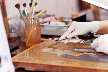 Art restorer working on the ancient  icon