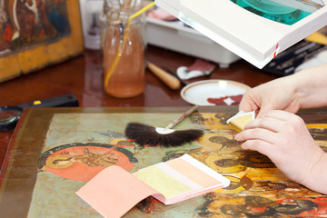 Restorer gilding on the ancient Christian icon