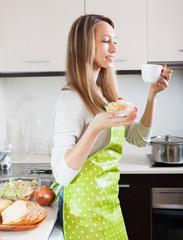 Blonde woman in apron drinking tea