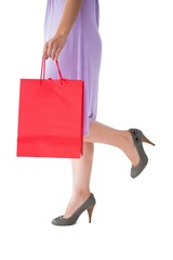 Mid section of woman holding red shopping bag