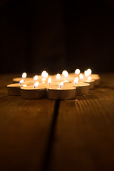 several candles burning in the dark on a wooden surface