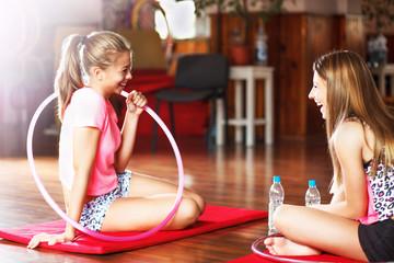 Teenage girls on training, with hula hoop, indoor