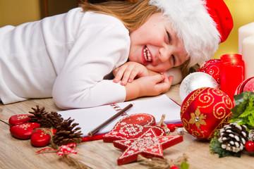 Funny girl in Santa hat writes letter to Santa near christmas de