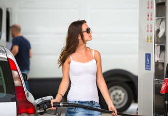 Attractive, young woman refueling her car in a gas station