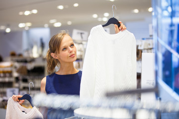 Beautiful young female shopper in a clothing store