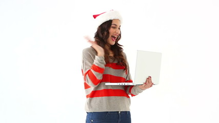 Pretty festive brunette chatting with someone online on laptop
