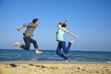 Chico y chica saltando en la playa muy animados