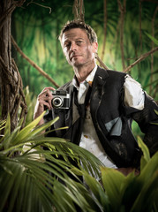Photoreporter walking in the jungle with vintage camera