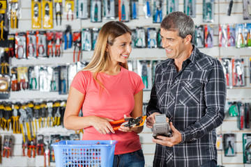 Couple Paying Pliers Through Smartphone In Hardware Store