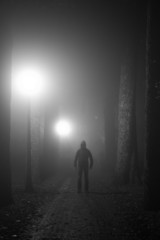 Scary man standing in a lane on a foggy night. Black and white.