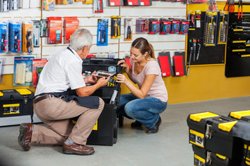 Salesman Showing Tools To Customer In Shop