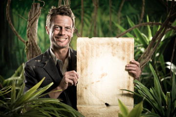 Businessman with old paper parchment in the jungle