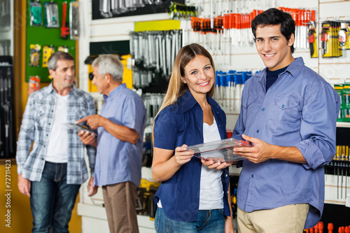 Happy Couple Holding Tool Set In Hardware Store - 72711423