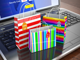 E-commerce concept. Colourful paper striped shopping bags on lap