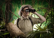 Leinwanddruck Bild - Explorer in the jungle with binoculars
