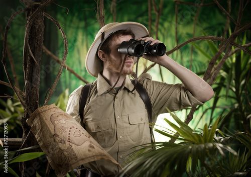 Leinwanddruck Bild Explorer in the jungle with binoculars