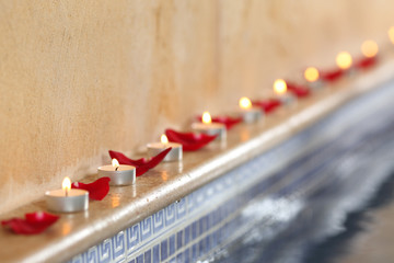 Candles and rose petals in a spa poolside relax concept