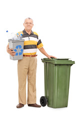 Senior holding recycle bin by a trash can