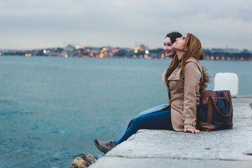 Two Women with Istanbul Cityscape on Background at Dusk