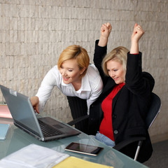 Successful managers in office with laptop