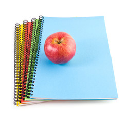 red apple and notebooks