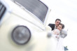 Happy bride and groom near retro car