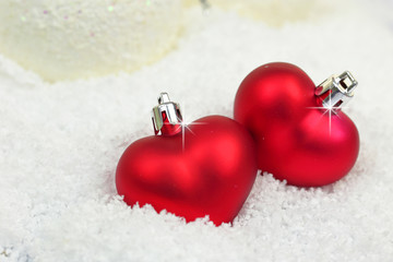 Two Christmas ornaments in shape of heart on snow