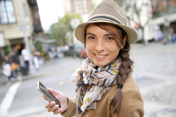 Trendy brunette girl in the street using smartphone