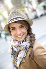 Portrait of smiling woman with scarf and hat in town