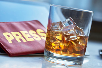 the mass media card, a glass of whiskey, tablet
