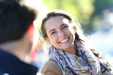 Portrait of cheerful girl pulling boyfriend by arm