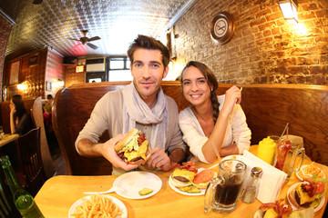 Couple in New York City eating hamburger in restaurant