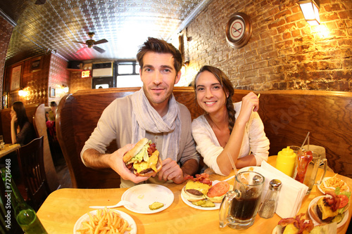 canvas print picture Couple in New York City eating hamburger in restaurant