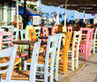 Obrazy na płótnie, fototapety, zdjęcia, fotoobrazy drukowane : Greek island restaurants with colorful tables and chairs.
