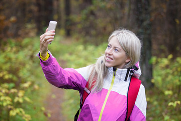Woman making selfie photo while hiking in forest