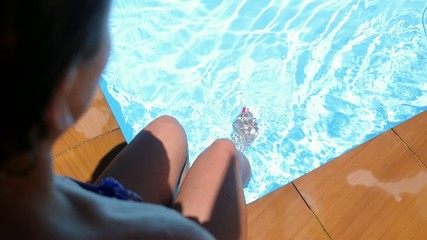 Female Foot in Blue Water of Swimming Pool. Slow Motion.