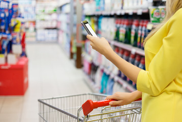 Woman checking shopping list on her smartphone at supermarket