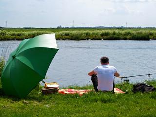 Fishing man with fishing rod and umbrella