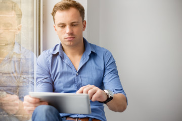 Young creative man sitting at window and using ipad