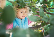 Portrait of cute blonde little girl playing outdoors