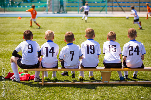 canvas print picture Football soccer match for children. Kids waiting on a bench.