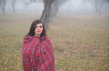 Girl foggy afternoon in a warm plaid