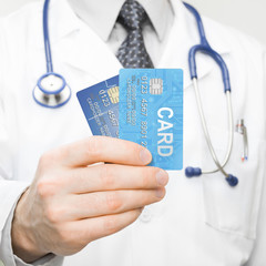 Doctor holding credit cards in his hand - closeup studio shot