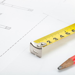 Measure tape and pencil over some documents