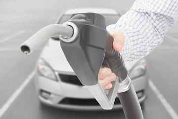 Black color fuel pump gun in hand with car on background