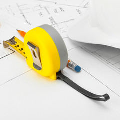 Yellow measure tape with gloves, construction helmet and pencil