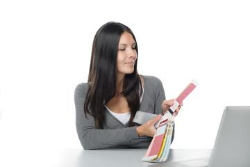 Junge Frau vergleicht Farben auf ihrem Computer