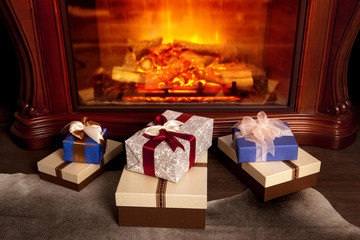 Christmas gift boxes near fireplace