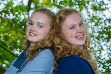 Two sisters heads together under green tree