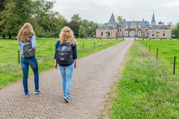Two tourists walking on road leading to castle